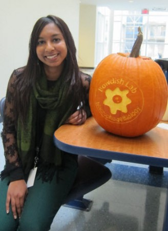 Aveshni Naidoo, MSc sits beside the coolest jack-o'-lantern ever.
